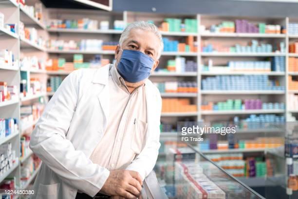portrait of male senior pharmacist with face mask at pharmacy - farmacêutico imagens e fotografias de stock