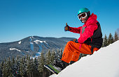 Portrait of male snowboarder sitting, relaxing on the snowy slope at winter ski resort in the mountains, showing thumbs up to the camera copyspace extreme lifestyle hobby sportsman recreation