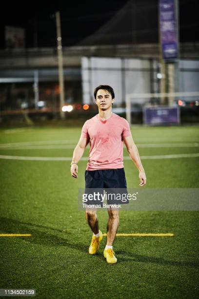 portrait of male soccer player walking on field during evening practice - black shorts stock pictures, royalty-free photos & images
