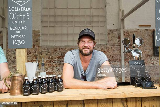 portrait of male stall holder on cooperative food market stall - market stall stock pictures, royalty-free photos & images