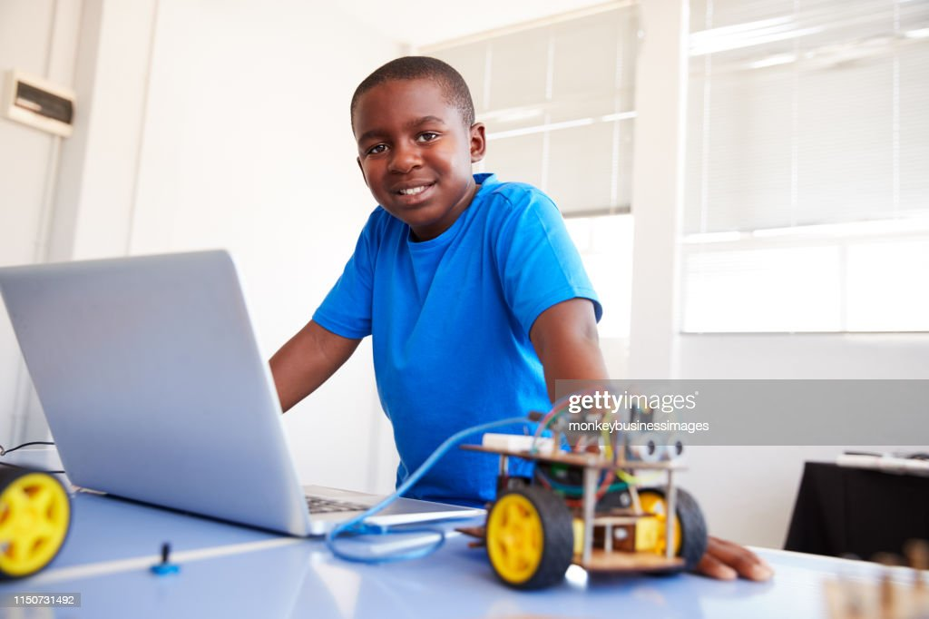 Portrait Of Male Student Building And Programing Robot Vehicle In School Computer Coding Class : Stock Photo
