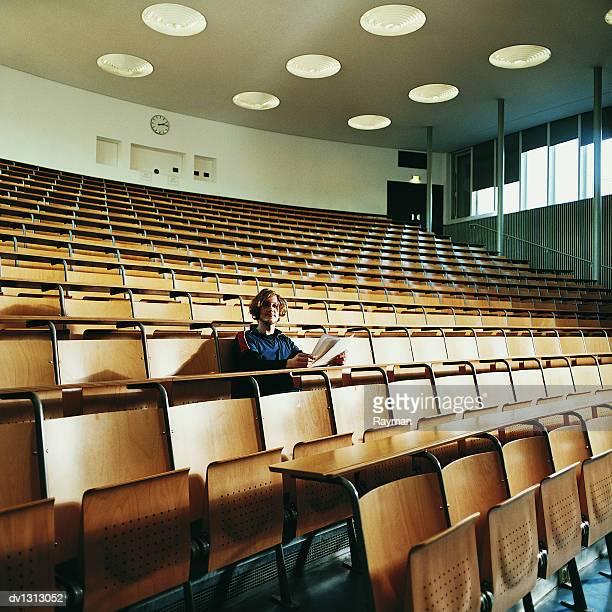 portrait of male student sitting in an empty lecture hall - hörsaal stock-fotos und bilder