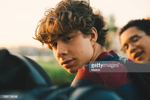 portrait of male teenager with friends standing in city - curly stock pictures, royalty-free photos & images