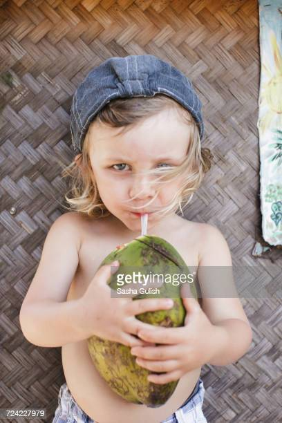 Portrait of male toddler in baseball cap drinking coconut milk