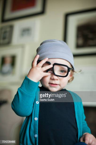 Portrait of male toddler in knit hat trying on eye glasses
