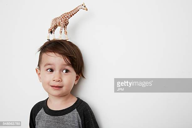Portrait of male toddler with toy giraffe on his head