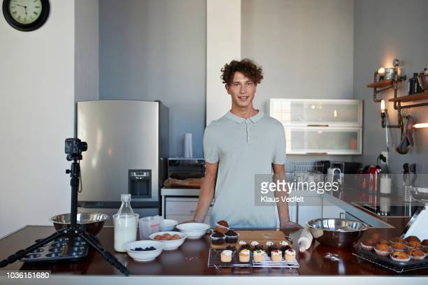 Portrait of male vlogger making video while baking in kitchen