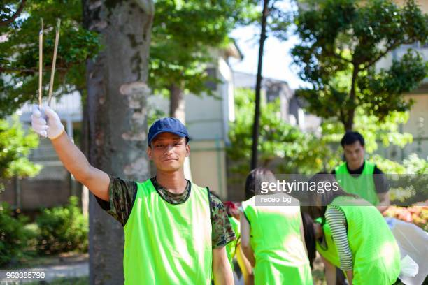 portrait of male volunteer in public park in tokyo - tongs work tool stock photos and pictures