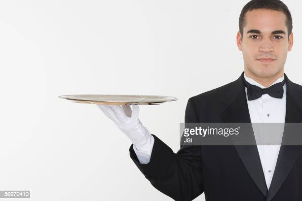 portrait of male waiter balancing tray - formal glove stock pictures, royalty-free photos & images