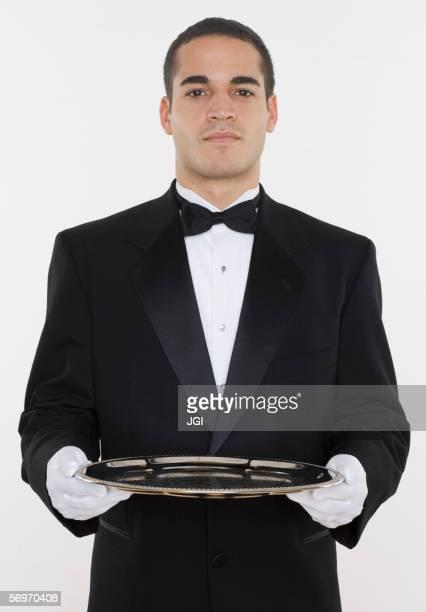 portrait of male waiter holding tray - smoking stock-fotos und bilder