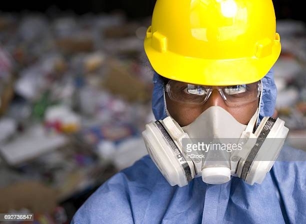 portrait of male worker in hard hat and gas mask, in front of rubbish at recycling plant - gas mask stock pictures, royalty-free photos & images