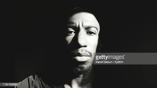 portrait of man against black background - datsun stock pictures, royalty-free photos & images