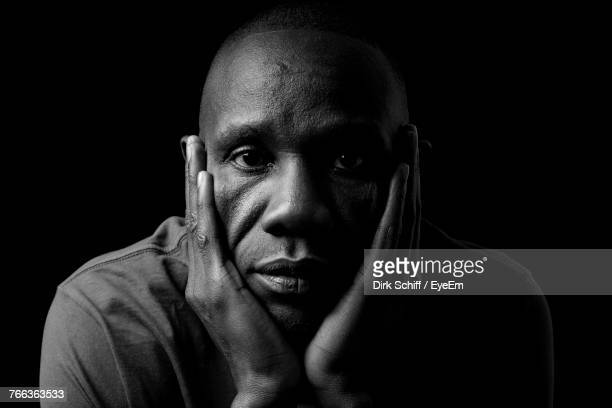 portrait of man against black background - black and white portrait stock photos and pictures