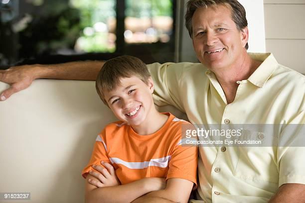 """portrait of man and boy smiling - """"compassionate eye"""" imagens e fotografias de stock"""