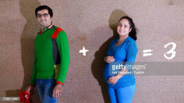 Portrait Of Man And Pregnant Woman Against Mathematical Equation On Wall