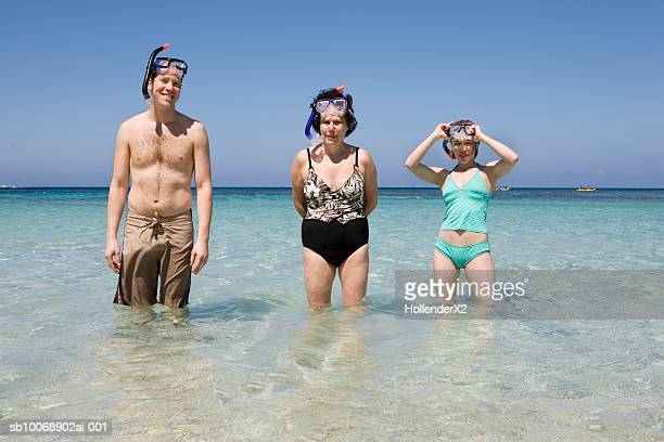 Portrait of man and two women with snorkeling gear in sea