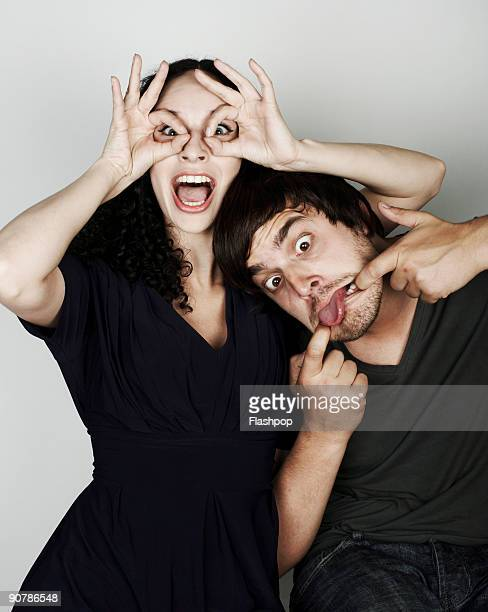 Portrait of man and woman pulling funny faces
