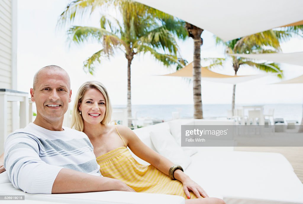 Portrait of man and woman relaxing at cafe nearby beach : Bildbanksbilder
