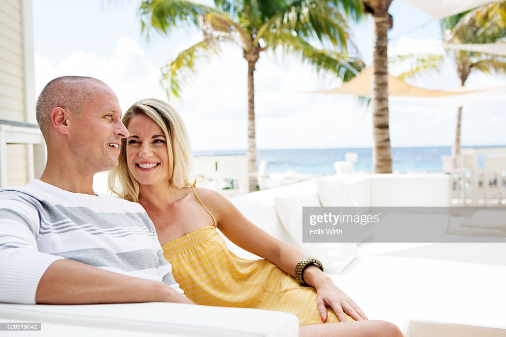 Portrait of man and woman relaxing at cafe nearby beach : Stockfoto