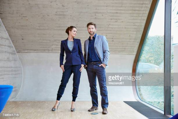 portrait of man and woman standing in attic office - bem vestido - fotografias e filmes do acervo