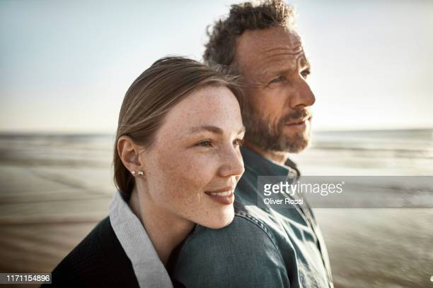 portrait of man and young woman by the sea - contemplation couple stock pictures, royalty-free photos & images
