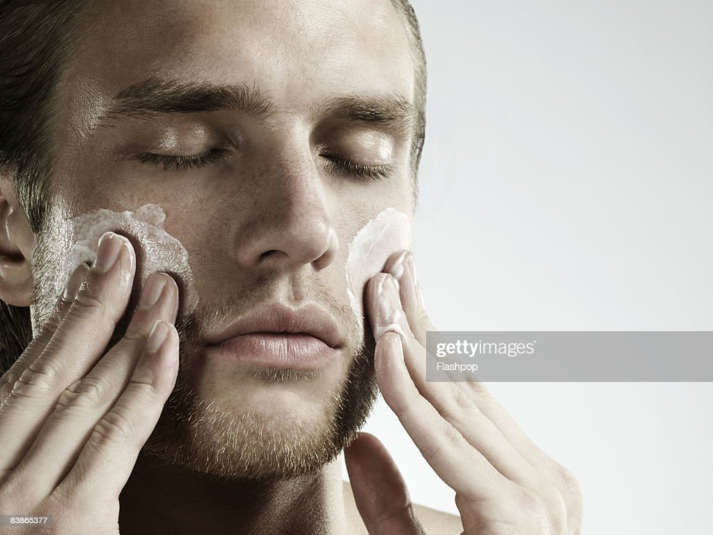 portrait of man applying moisturizer to face : Stock Photo