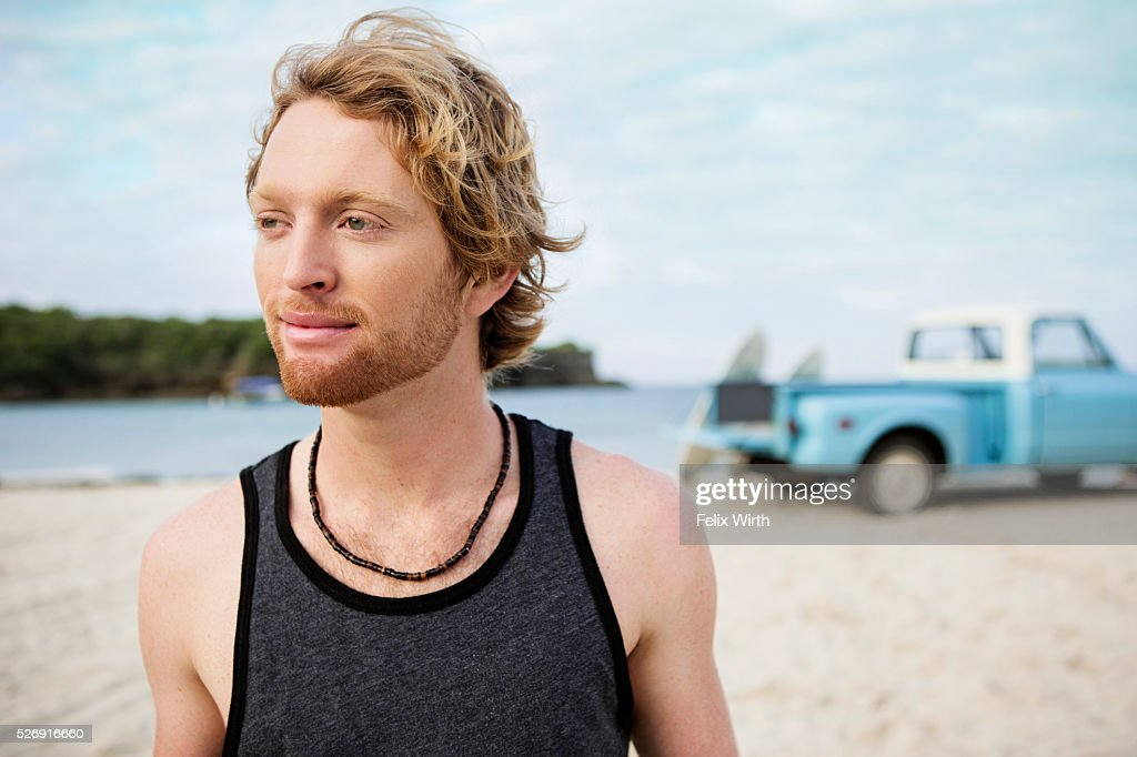 Portrait of man at beach, with pickup truck in background : Stockfoto