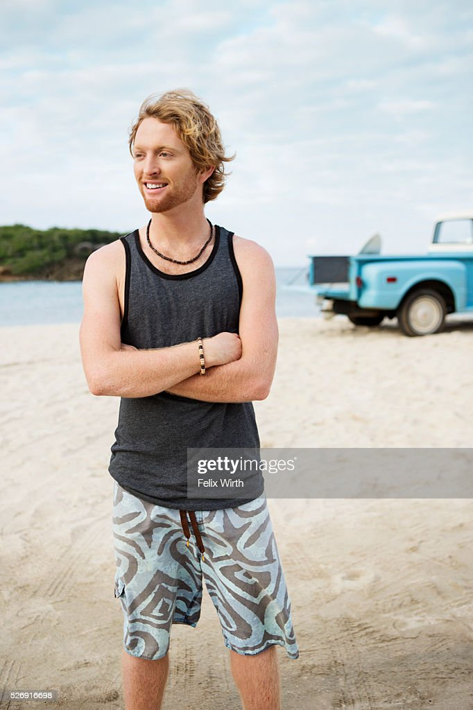 Portrait of man at beach, with pickup truck in background : Photo