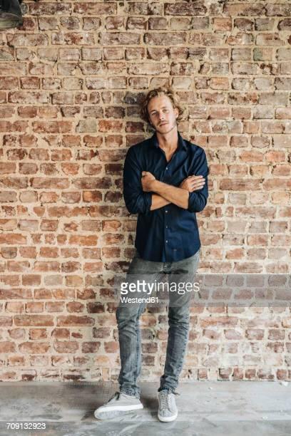 Portrait of man at brick wall