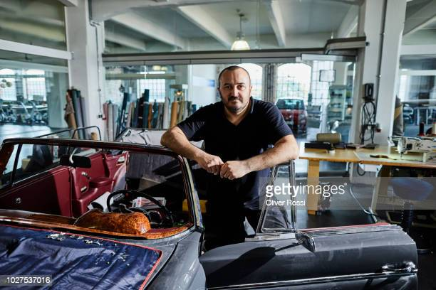 portrait of man at vintage car in an automobile upholstery workshop - vintage auto repair stock pictures, royalty-free photos & images