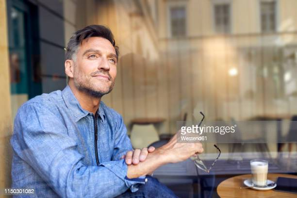 portrait of man behind windowpane in a cafe - looking away stock pictures, royalty-free photos & images