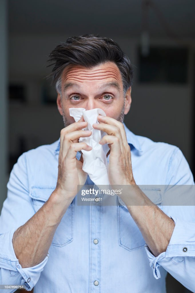 Portrait of man blowing nose : Foto de stock
