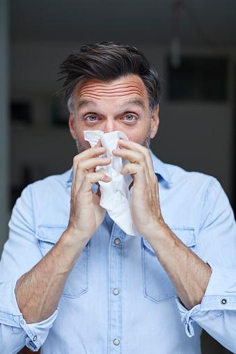 Portrait of man blowing nose - gettyimageskorea