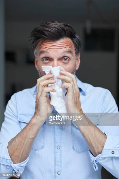 portrait of man blowing nose - handkerchief - fotografias e filmes do acervo
