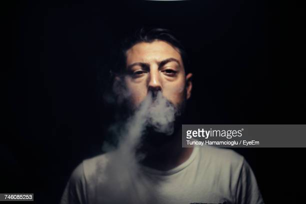 Portrait Of Man Blowing Smoke Against Black Background
