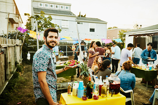 Portrait of man bringing food to table during backyard party with friends on summer evening - gettyimageskorea