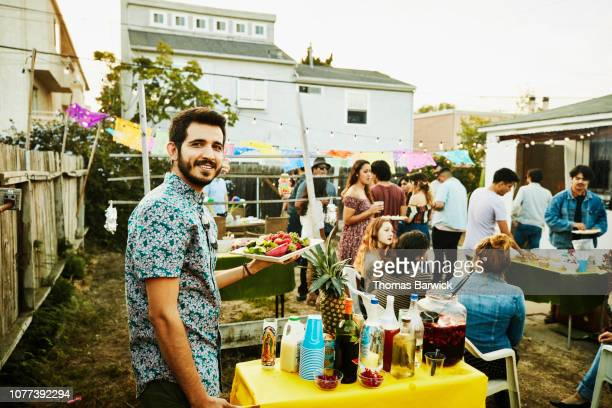 portrait of man bringing food to table during backyard party with friends on summer evening - mexican ethnicity stock pictures, royalty-free photos & images