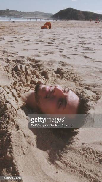 Portrait Of Man Buried In Sand At Beach