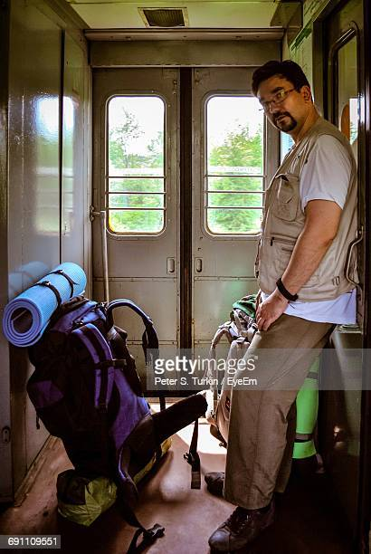 Portrait Of Man By Backpack Standing In Train