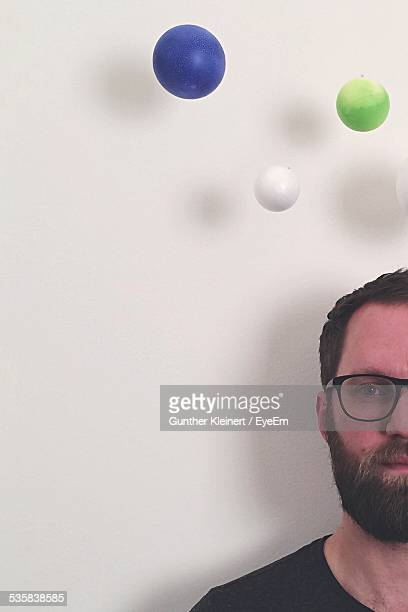 Portrait Of Man By Multi Colored Balls Against Wall