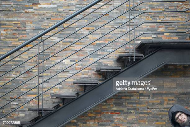 portrait of man by staircase on wall - adriana duduleanu stock photos and pictures