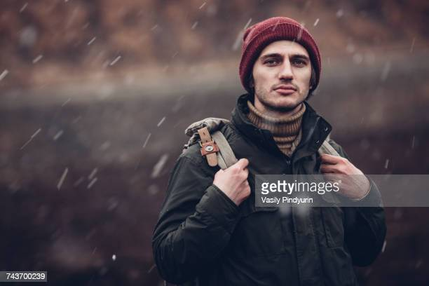 Portrait of man carrying backpack while standing outdoors during snowfall