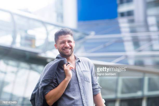 portrait of man carrying jacket over shoulder looking at camera smiling - sigrid gombert stock pictures, royalty-free photos & images