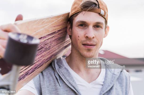 portrait of man carrying skateboard - skateboard stock-fotos und bilder