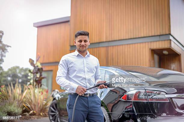 Portrait of man charging electric car