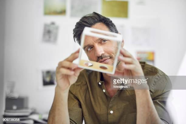portrait of man checking component in his office - kontrolle stock-fotos und bilder