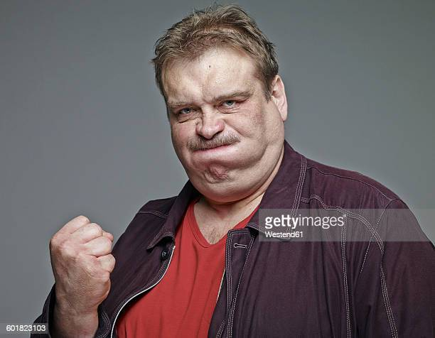 portrait of man clenching his fist in front of grey background - sour taste stock pictures, royalty-free photos & images