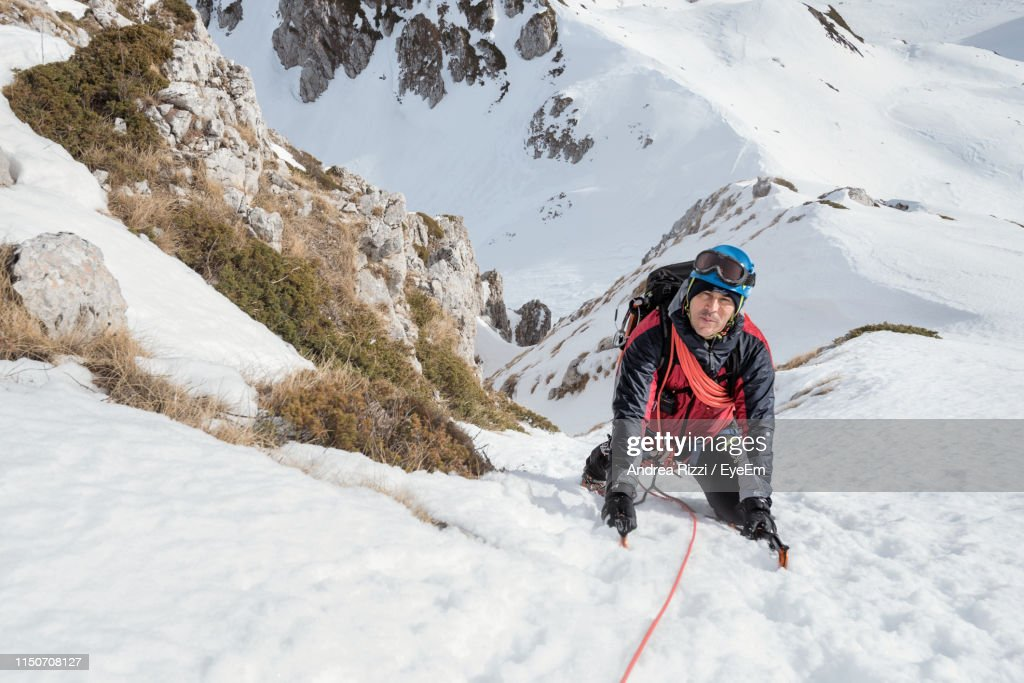 Portrait Of Man Climbing Snow Covered Mountain : Stock Photo
