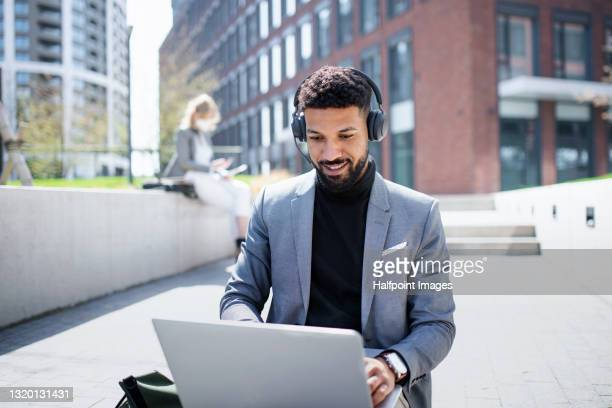 portrait of man commuter using laptop in city, video call concept. - formal stock pictures, royalty-free photos & images