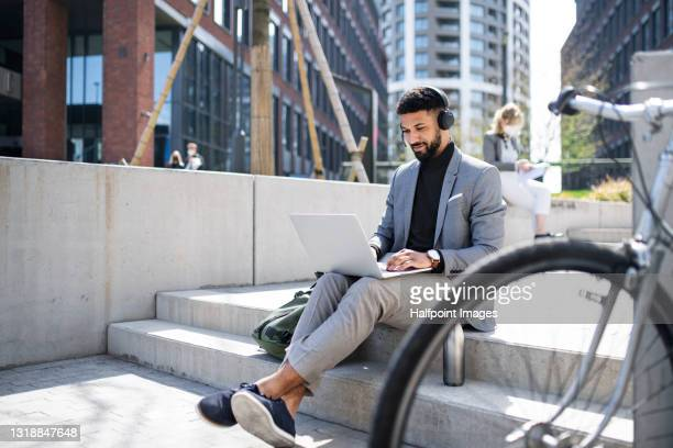 portrait of man commuter with bicycle using laptop in city. - commuter stock pictures, royalty-free photos & images
